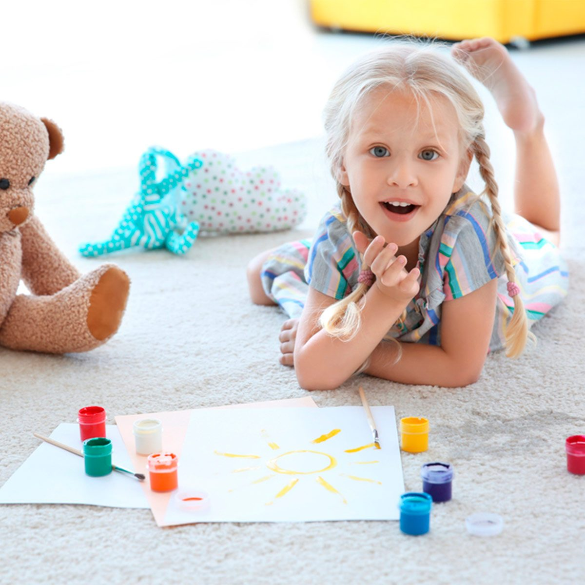 little girl painting on carpet