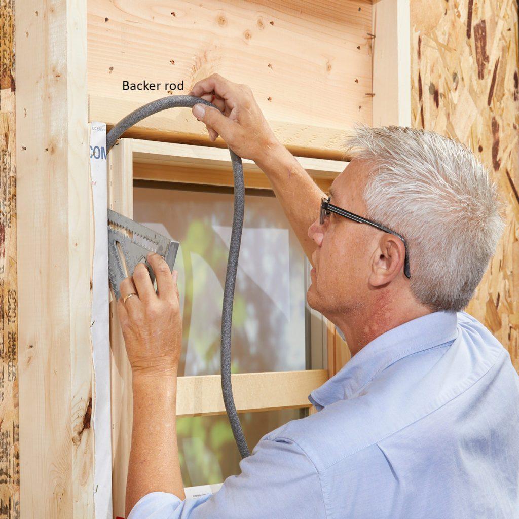 Man installing backer rod in window cavities | Construction Pro Tips