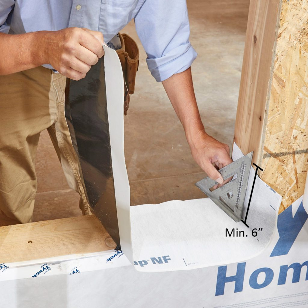 Man installing window pan flashing on window sill | Construction Pro Tips