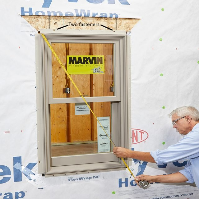 Man squaring and fastening the window with a measuring tape | Construction Pro Tips