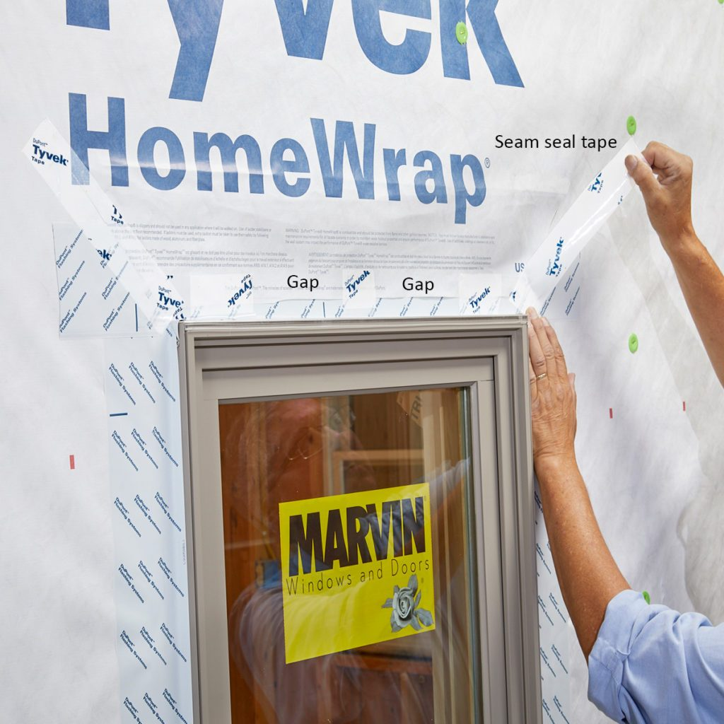 Taping the top flaps of Tyvek down after window installation | Construction Pro Tips