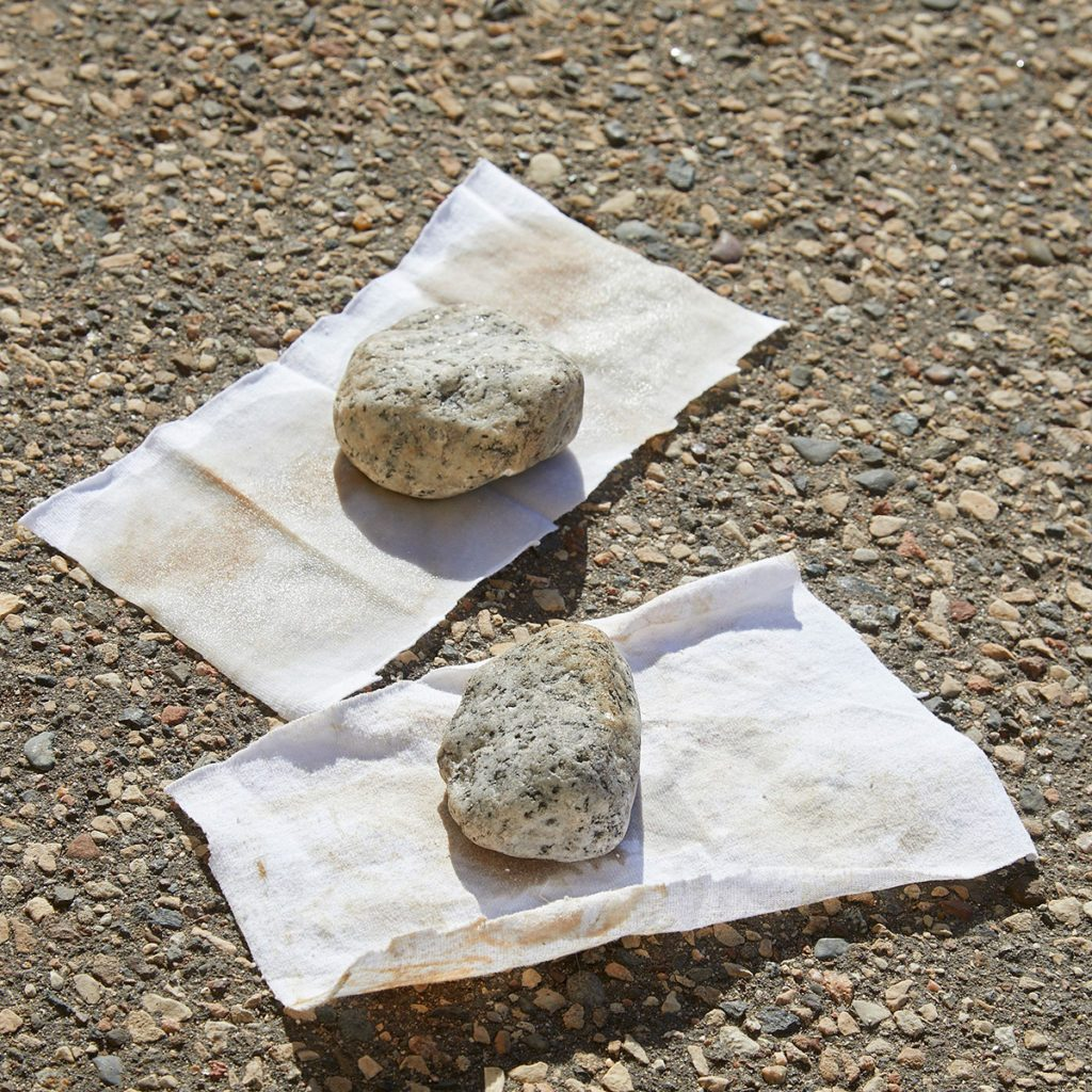 Rocks weighing down two oily rags on ground   Construction Pro Tips