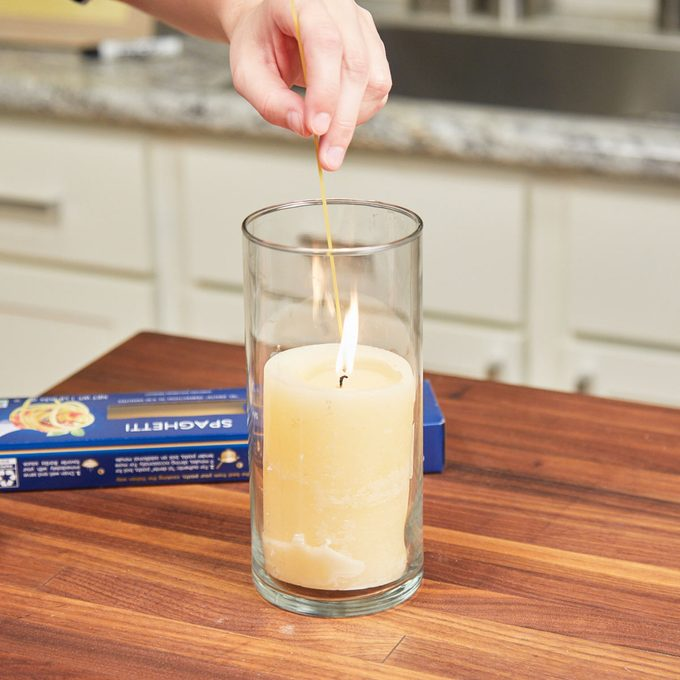 Hand holding a spaghetti noodle as a candle lighter from Family Handyman