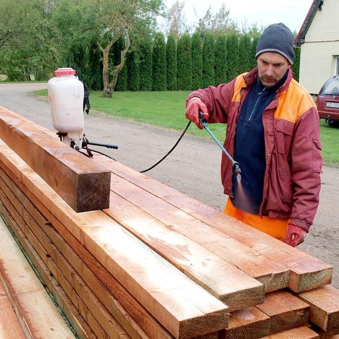 Man spraying treatment onto lumber   Construction Pro Tips