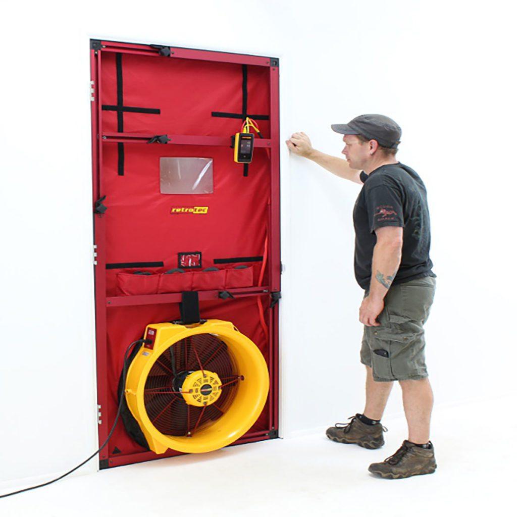 Man standing next to blower door test | Construction Pro Tips