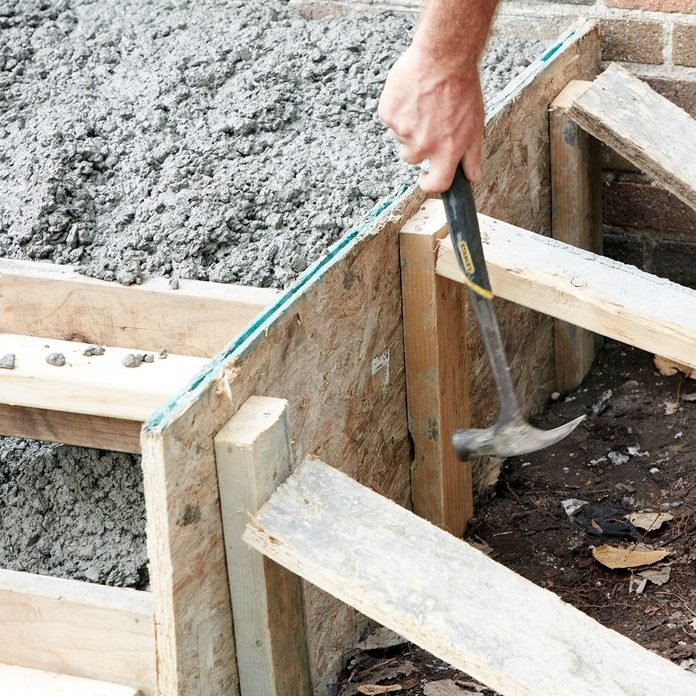Tapping on the sides of the forms to get concrete to settle | Construction Pro Tips