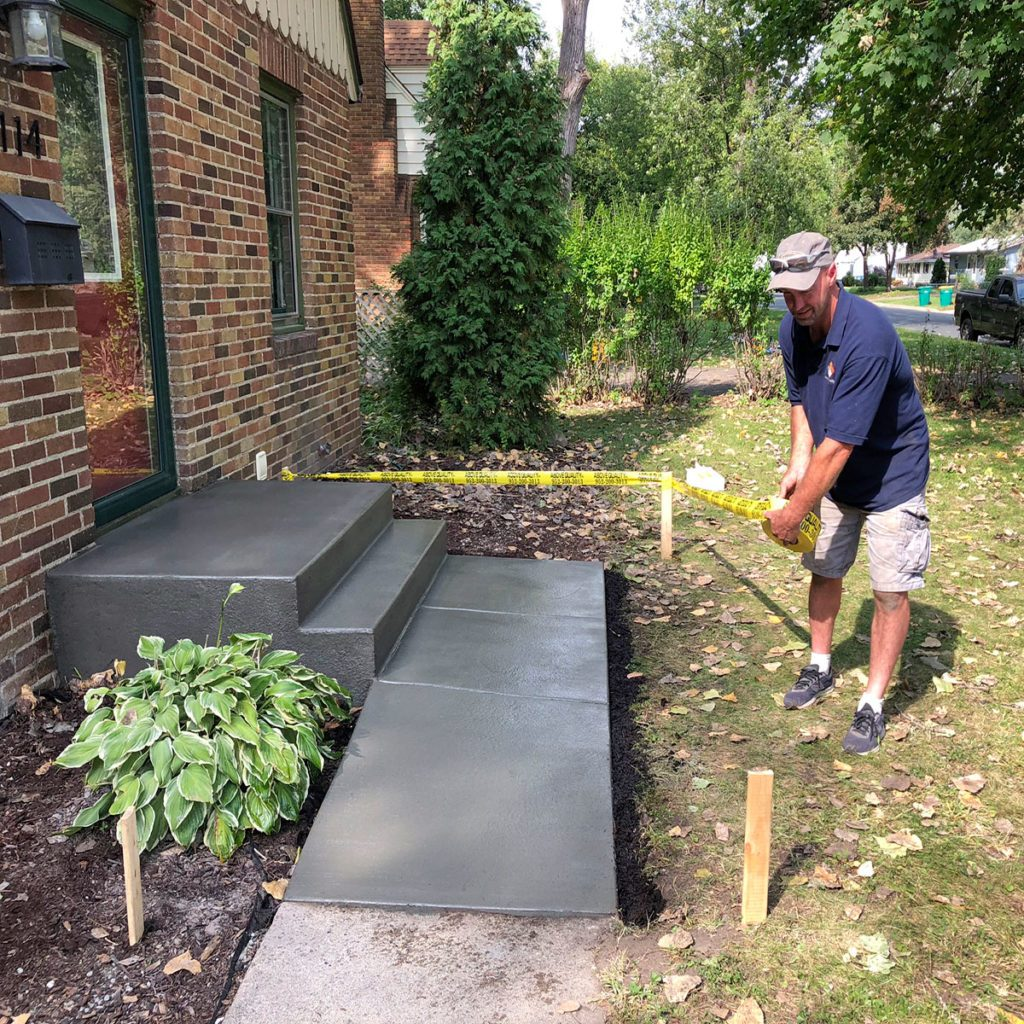 Man placing a tape barricade around a new concrete step | Construction Pro Tips