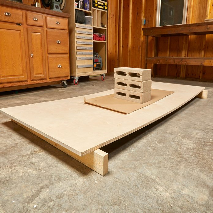 Removing the bow from plywood with cinderblocks | Construction Pro Tips