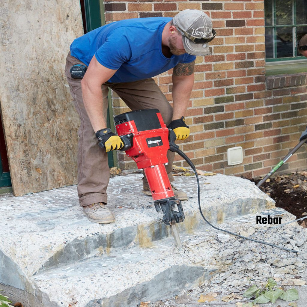 Breaking down an old step with a jackhammer | Construction Pro Tips
