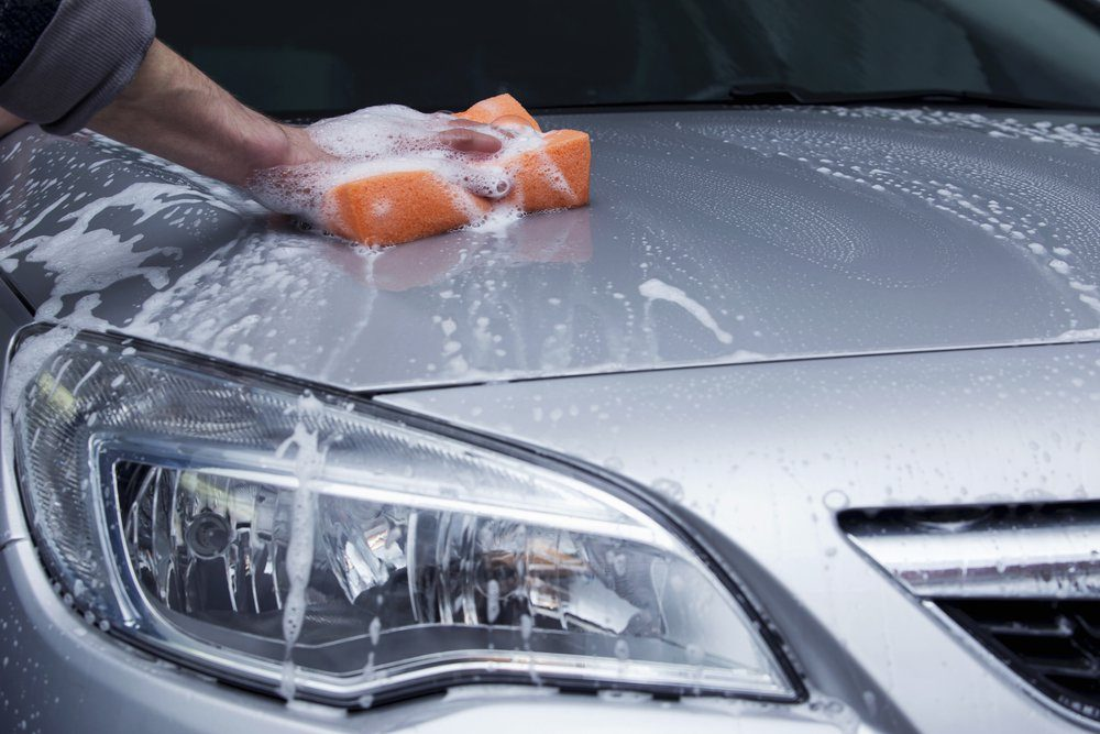 a silver car is washing in soap suds