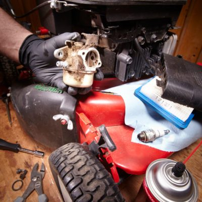lawn mower carburetor being removed for inspection