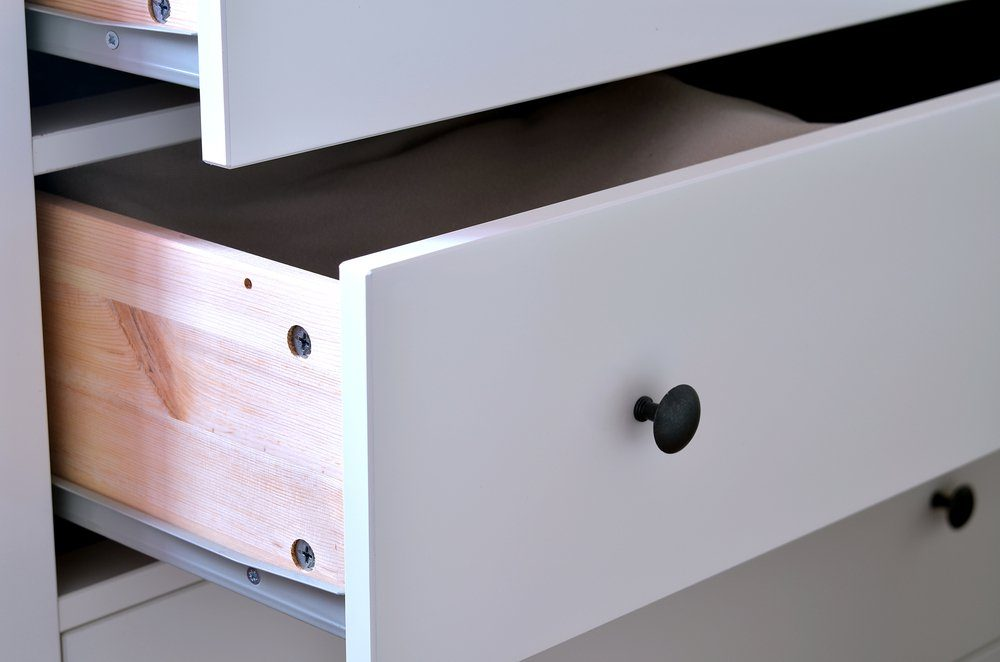 Detail of open white laminated drawer with brass handle