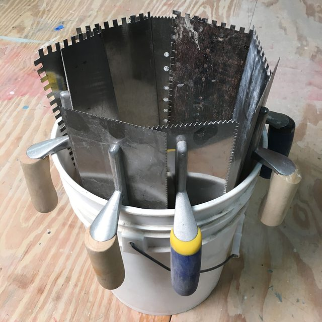 Trowels hooked onto the edge of a bucket | Construction Pro Tips