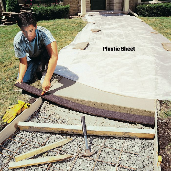 Man laying plastic sheets over concrete   Construction Pro Tips