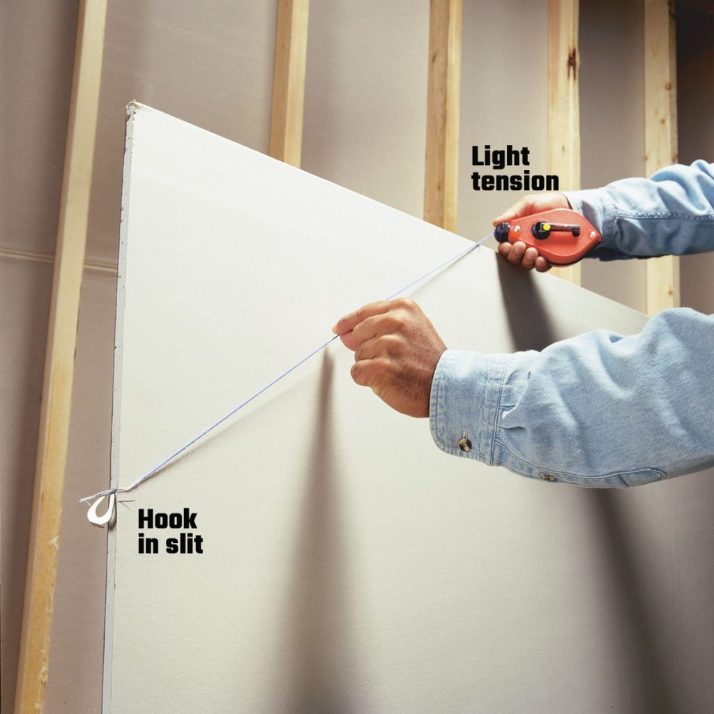 Making a line on a piece of drywall with a chalk line | Construction Pro Tips