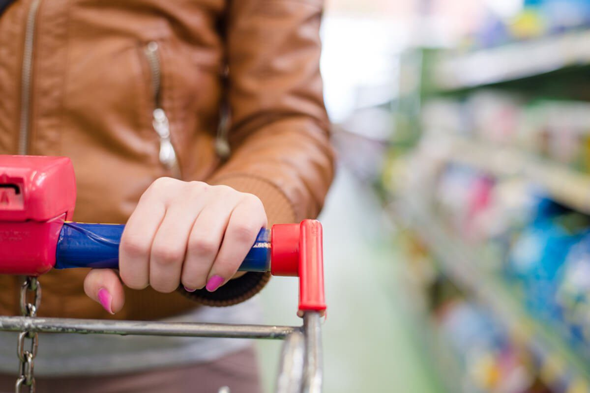 close up on hand of a woman on a supermarket trolley carries