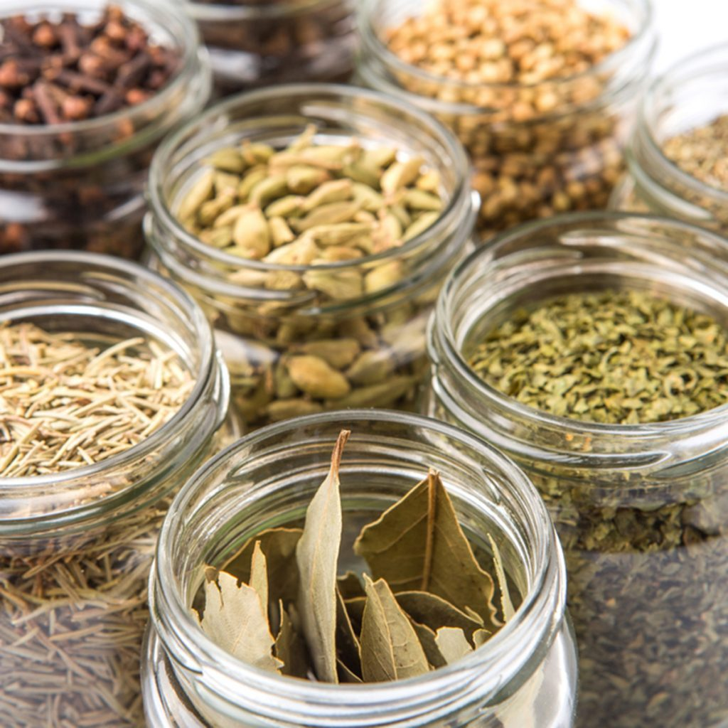 Cardamom, star anise, cinnamon, clove, coriander seed spices and dried bay leaves, parsley, thyme, rosemary herbs in mason jars over white background; Shutterstock ID 293429393; Job (TFH, TOH, RD, BNB, CWM, CM): Taste of Home