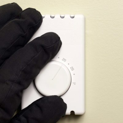 hand with glove changing thermostat