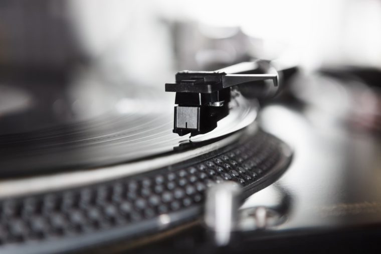 Dj turntable player playing vinyl record disc with hip hop music.Closeup,focus on needle cartridge headshell.Disc jockey audio equipment for scratch.Hifi sound system