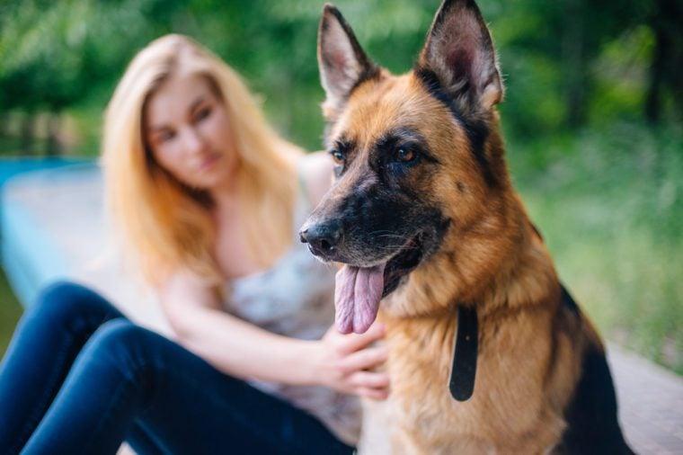 female with german shepherd dog in park
