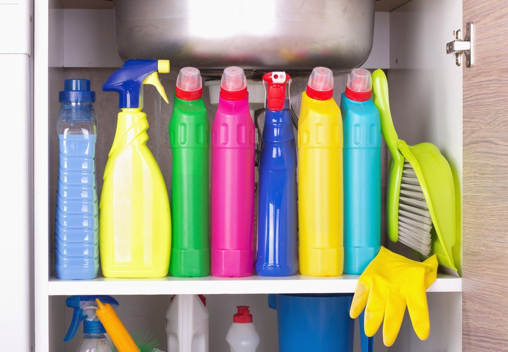 Cleaning products placed in kitchen cabinet under sink. Housekeeping storage space