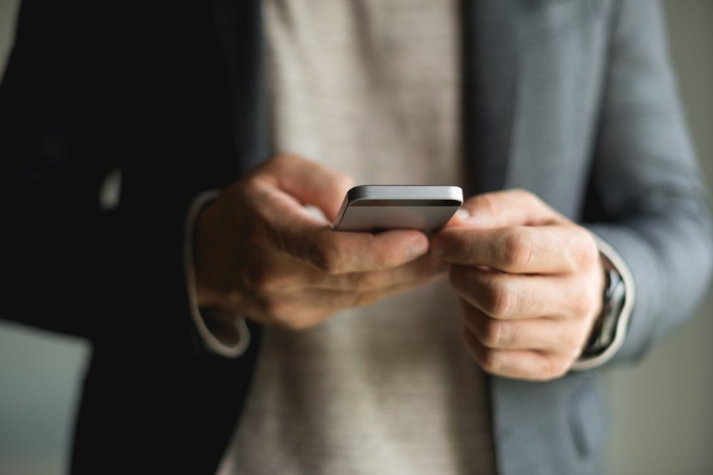 Businessman Typing on smart phone