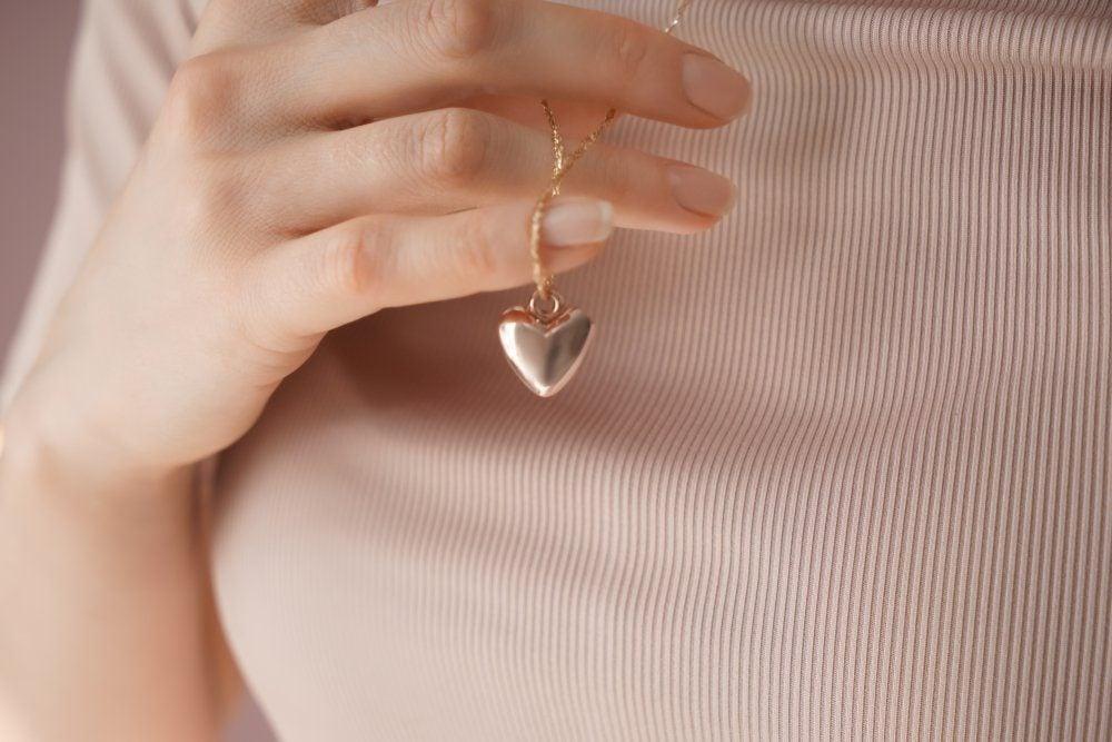 Woman wearing heart-shaped pendant, closeup