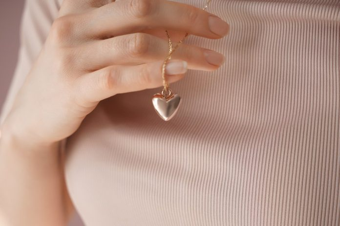 Woman wearing heart-shaped pendant, closeup