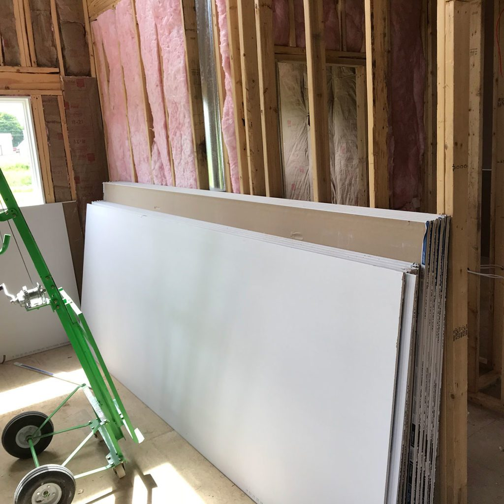 Drywall stacked against bare framing | Construction Pro Tips