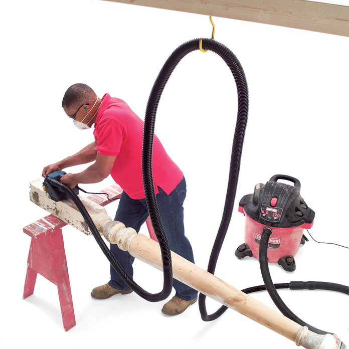 Man using a dust control system handing from a ceiling hook | Construction Pro Tips