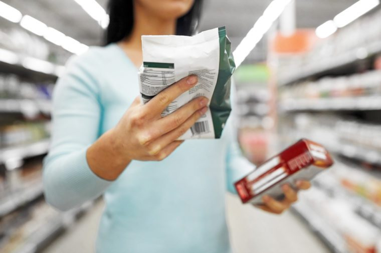 sale, shopping, consumerism and people concept - close up of woman with food at grocery store