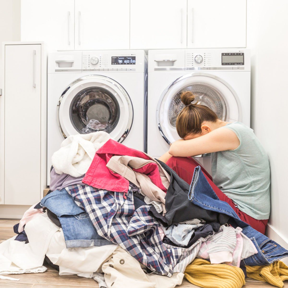 Sad woman sitting in laudry room with a pile of dirty clothes; Shutterstock ID 775801702; Job (TFH, TOH, RD, BNB, CWM, CM): Taste of Home