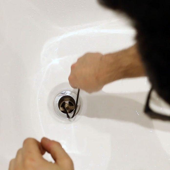 Shoving a cut zip tie into a bathtub drain | Construction Pro Tips