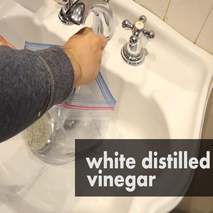 White distilled vinegar in a bag with a shower head | Construction Pro Tips