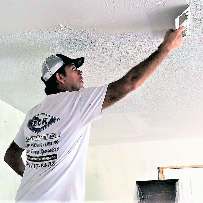 Man applying skim coating to a ceiling | Construction Pro Tips