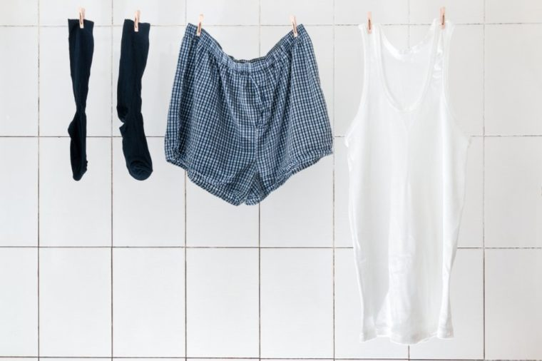 Men's briefs socks and shirts weigh in the bathroom on the rope to dry. Linen for every day of the week, linens for every day, bachelor panties, family panties