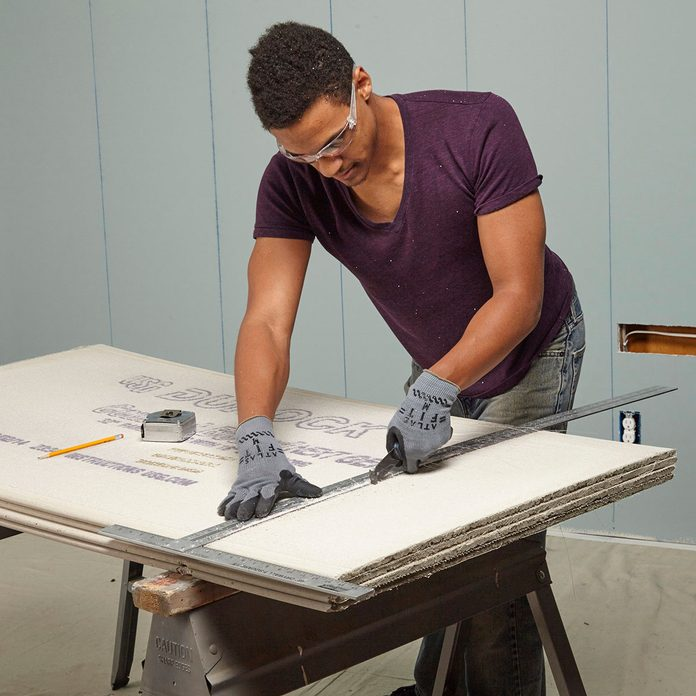 Man scoring a straight line into cement board   Construction Pro Tips