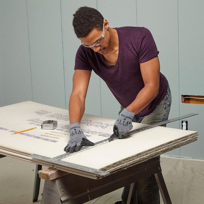 Man scoring a straight line into cement board | Construction Pro Tips