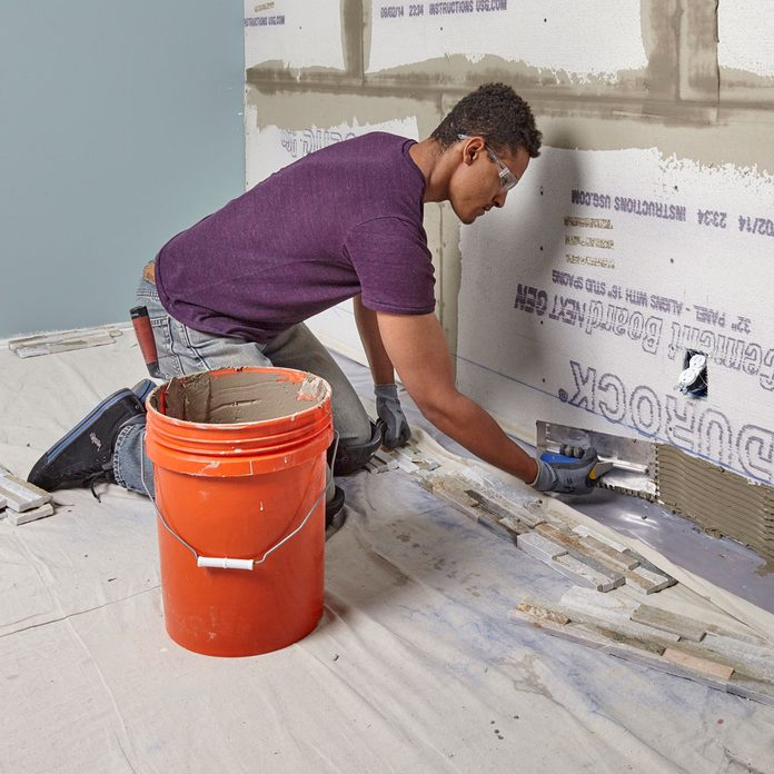 Spread thin-set along the bottom part of the wall   Construction Pro Tips