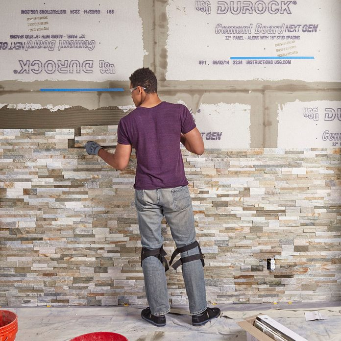 Laying the stone further and further up the wall   Construction Pro Tips