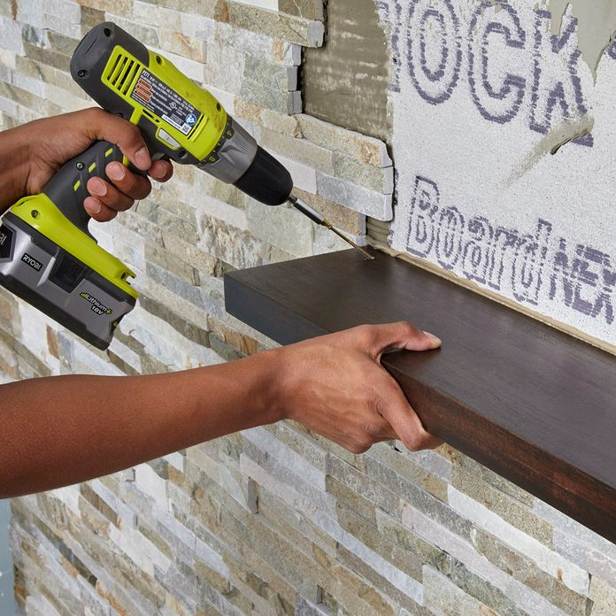 Attaching a shelf during stone wall installation   Construction Pro Tips