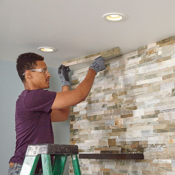 Cutting and placing the top line of stone on the wall   Construction Pro Tips