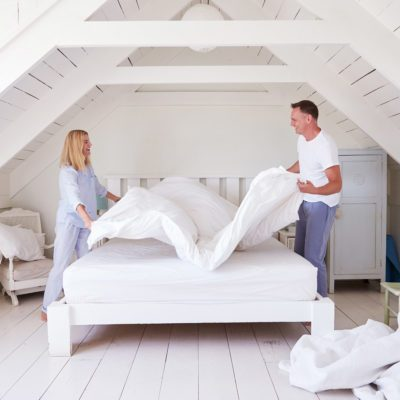 couple making the bed bedroom
