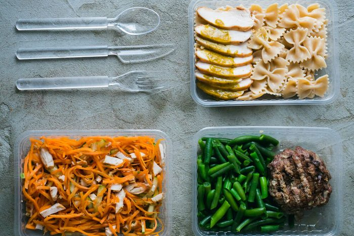 Food in plastic boxes, Daily meal plan delivery service. Fitness food cooked: beef with green beans, pasta with chicken, carrot salad