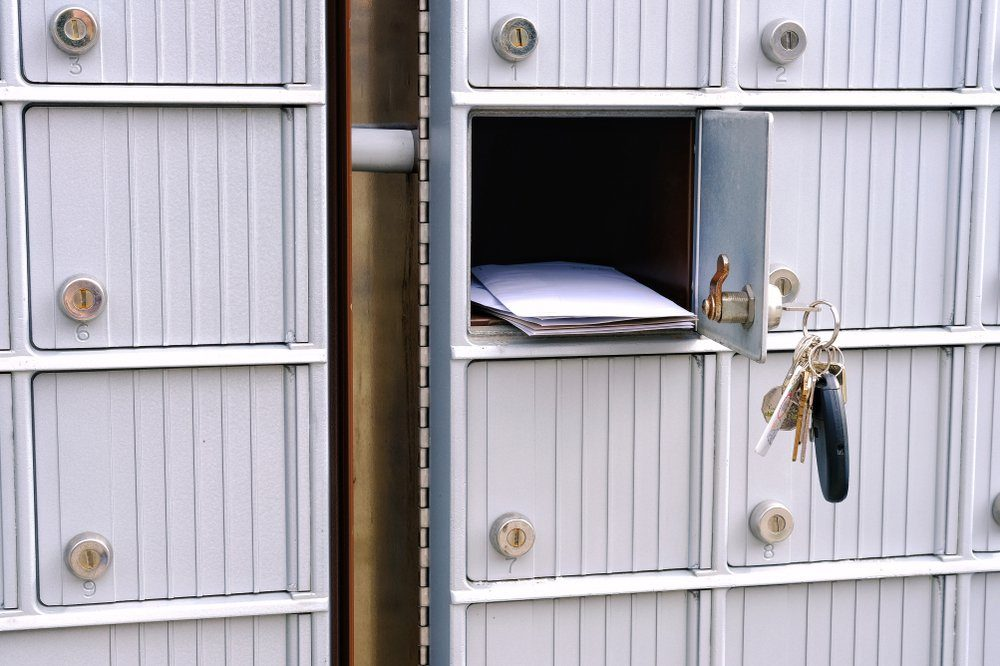 Open suburban mailbox door with keys dangling and mail visible in opening