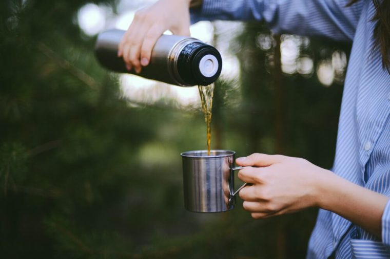 Traveler girl pouring tea from thermos cup, outdoors. Young woman drinking tea at cup. Theme travel. Woman pouring a hot drink in mug from thermos. Girl drinking tea during hike