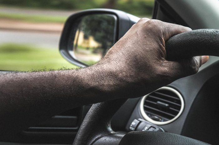 African Male hands on the steering wheel of a car while driving.Driver holding steering wheel. Black Man hands holding a steering wheel confidently. Hands on wheel - Man driving car - Africa