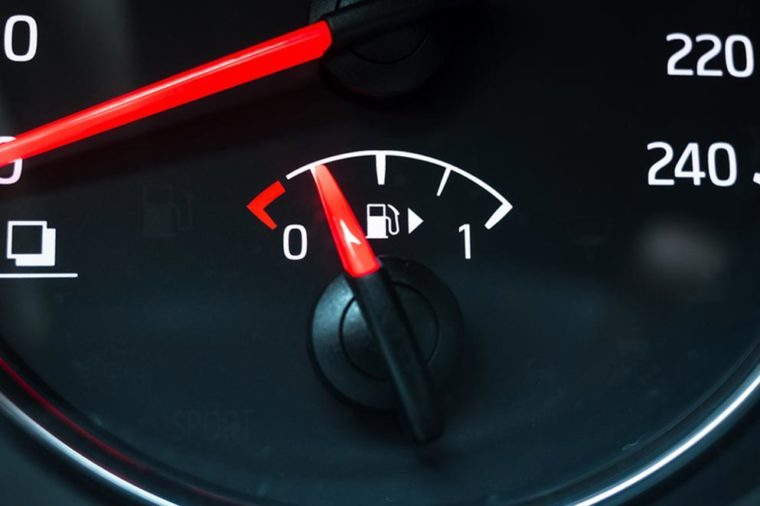 Fuel gauge mounted in round modern car speedometer shows low level of gasoline
