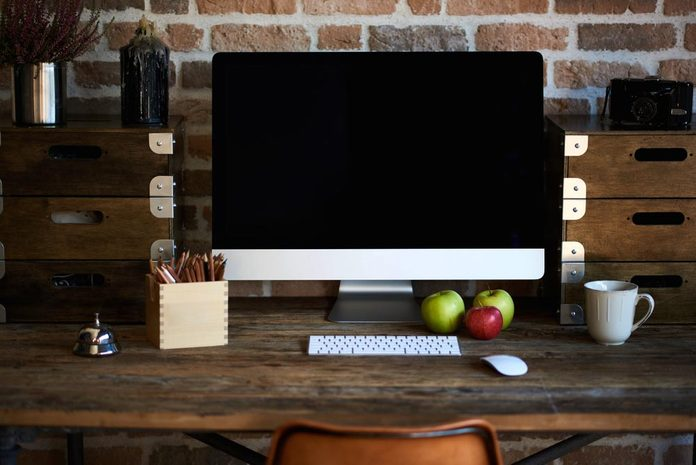 Desktop in modern loft interior with advanced computer for perfect creative freelance work and stationary, mock up PC standing near cup of coffee and croissant for breakfast in co working office