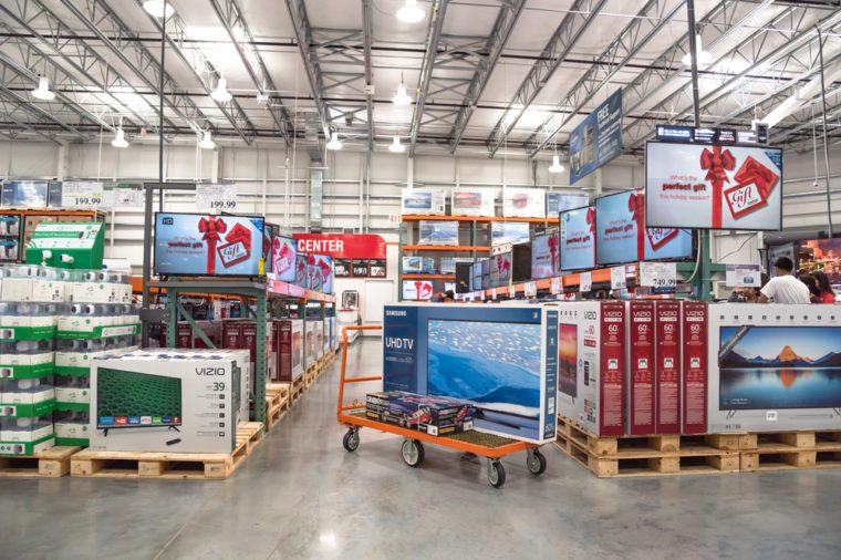 HUMBLE, TX, US-NOV 25, 2016: Costco Wholesale with row of big screen, smart TVs display on shelves and on flatbed cart. It is the largest membership-only warehouse club in US. Customer shopping.